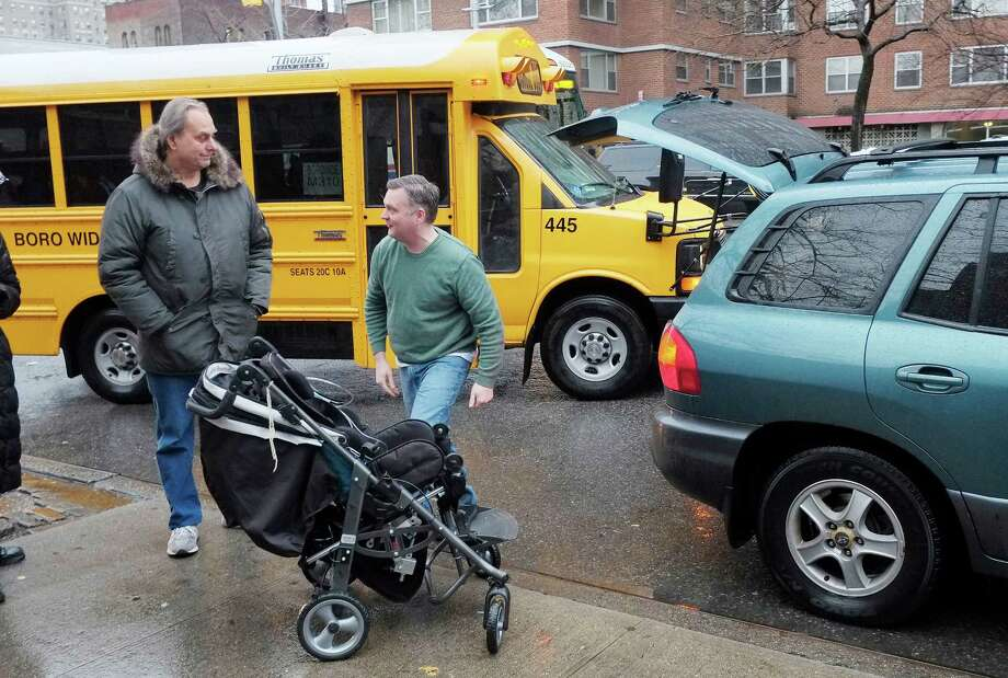 Peter Curry, center, unloads his daughter's wheel chair from his car after driving her to Public School 33, Wednesday, Jan. 16, 2013 in New York. She would normally be driven by school bus, according to her father. More than 8,000 New York City school bus drivers and aides went on strike over job protection Wednesday morning, leaving some 152,000 students, many disabled, trying to find other ways to get to school. (AP Photo/Mark Lennihan) Photo: Mark Lennihan