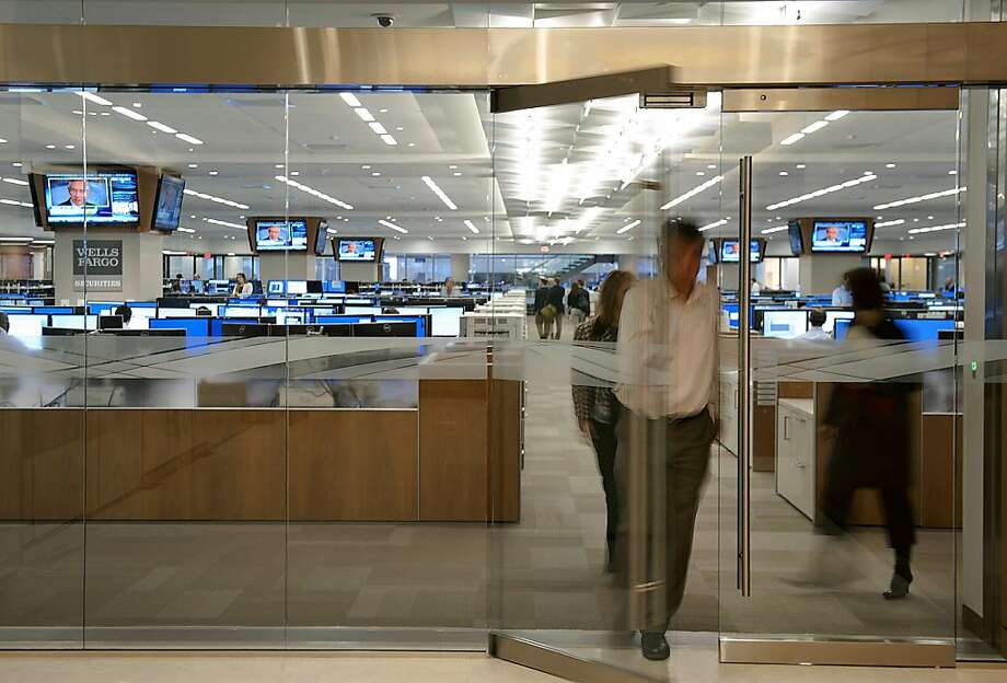 Wells Fargo traders, above, settle in to their new offices in the Duke Energy Center, right, in Charlotte, N.C. The move is an outgrowth of the bank's 2008 acquisition of Wachovia. Photo: Davis Turner, Bloomberg