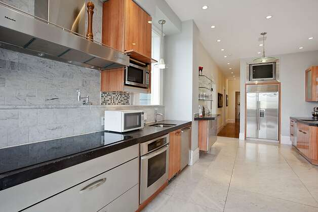 The main kitchen has four separate work spaces and concrete countertops. Photo: OpenHomesPhotography.com