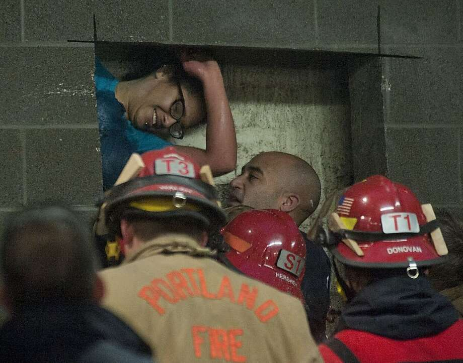 A woman is rescued from being trapped inside a wall of the parking garage at the Gretchen Kafoury Commons in SW Portland, Ore., Wednesday, Jan. 16, 2013. Portland firefighters worked for over three and a half hours cutting her free. Photo: Brent Wojahn, Associated Press