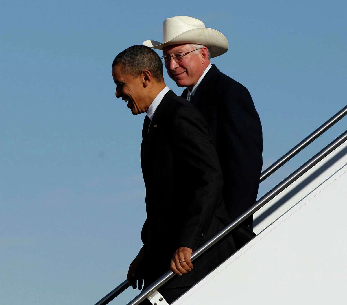 President Barack Obama, left, with Interior Secretary Ken Salazar, right, walk down the stairs during their arrival at Roswell International Air Center airport, March, 21, 2012 in Roswell, N.M.