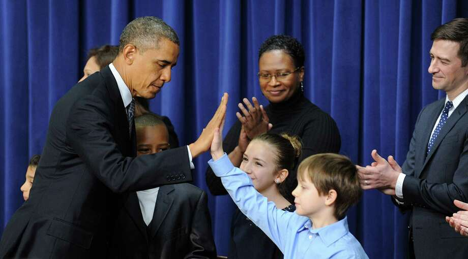 President Barack Obama gives a high-five to Grant Fritz after signing a series of executive orders about the administration's new gun law proposals in the Eisenhower Executive Office building Wednesday. Photo: Olivier Douliery, MBR / Abaca Press