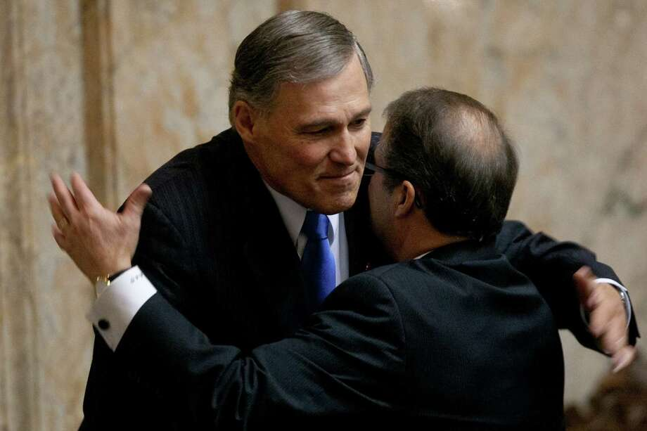 Washington State Governor Jay Inslee is embraced by Lt. Governor Brad Owens during his inaugural address. Photo: JOSHUA TRUJILLO, SEATTLEPI.COM / SEATTLEPI.COM