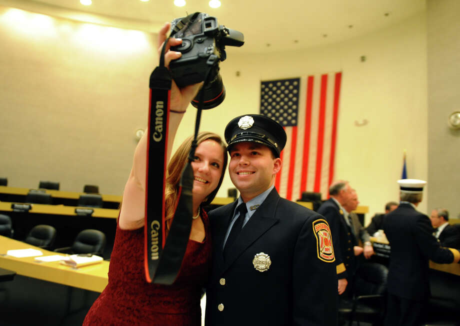 Newly sworn in Bridgeport firefighter Nicholas Porzelt poses for a photo with his girlfriend Jennifer Royals, after the ceremony conducted by the Board of Fire Commissioners in the Bridgeport City Council Chambers in Bridgeport, Conn. on Wednesday January 16, 2013. The group graduated from the Connecticut Fire Academy last month and will continue their EMS training in Bridgeport. Photo: Christian Abraham / Connecticut Post