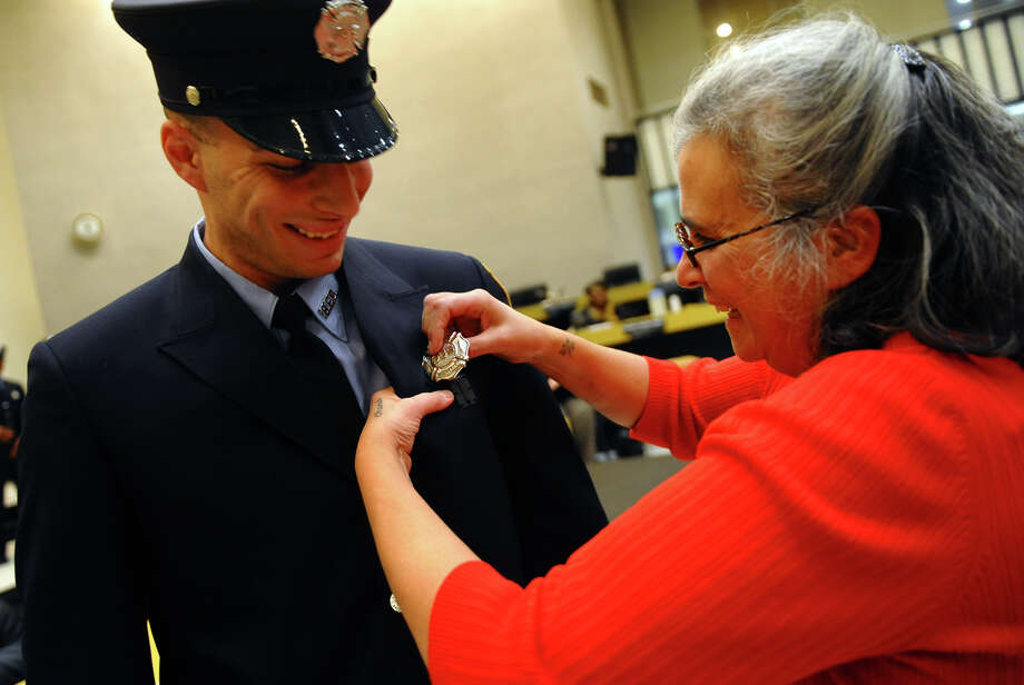 Proud mom Margherita Currao pins on Bridgeport firefighter Derek Currao's badge, during the swearing in ceremony conducted by the Board of Fire Commissioners in the Bridgeport City Council Chambers in Bridgeport, Conn. on Wednesday January 16, 2013. The 21 firefighters graduated from the Connecticut Fire Academy last month and will continue their EMS training in Bridgeport. Photo: Christian Abraham / Connecticut Post