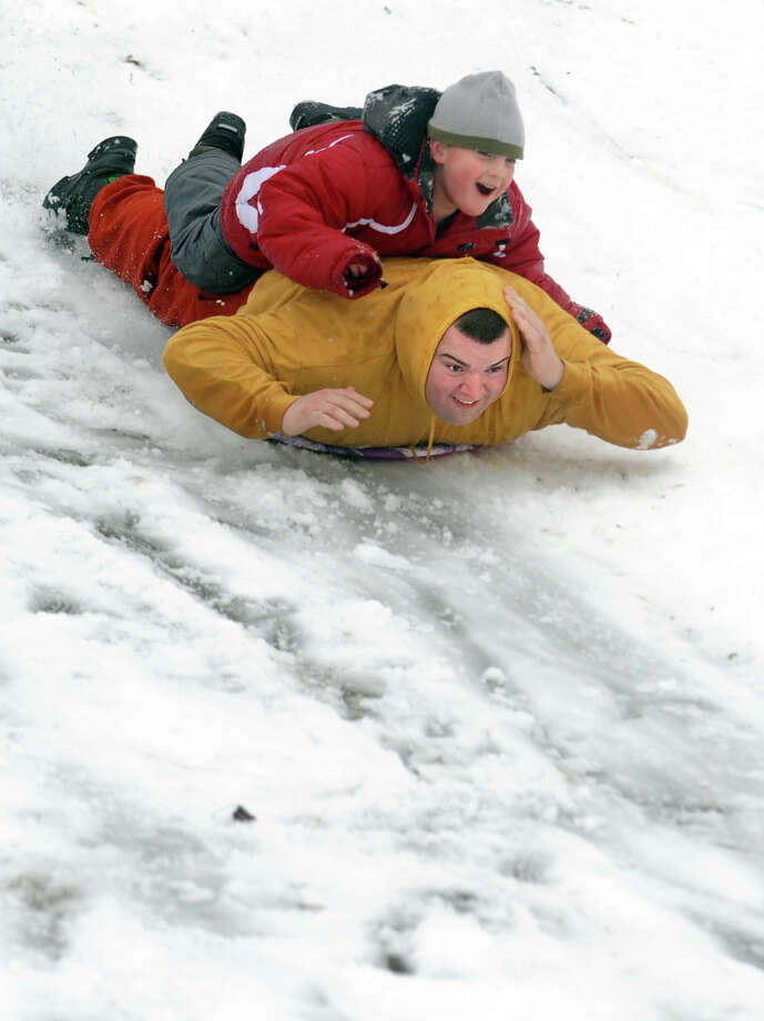Six-year-old Daniel Mascolo Jr., of Ansonia, sleds down the hill behind Derby Middle School on his father's back Wednesday, Jan. 16, 2013 in Derby, Conn. Photo: Autumn Driscoll / Connecticut Post
