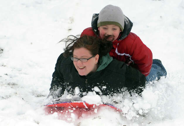 Norell Mascolo and her stepson, Daniel Mascolo Jr., 6, of Ansonia, sled down the hill behind Derby Middle School Wednesday, Jan. 16, 2013 in Derby, Conn. Photo: Autumn Driscoll / Connecticut Post