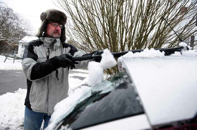 Gordon Shelp clears the snow from his car Wednesday, Jan. 16, 2013 in Ansonia, Conn. Photo: Autumn Driscoll / Connecticut Post