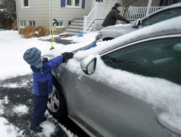 Tyler Wilhelm helps his dad, Mark, clean snow off the family cars  in their driveway in Fairfield, Conn. on Wednesday, Jan. 16, 2013. A wintery mix fell overnight making for a messy morning commute in Connecticut. Photo: Cathy Zuraw / Connecticut Post