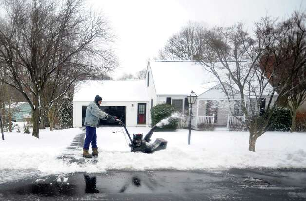 Ed Petitti cleans his neighbor's driveway on Reid St. in Fairfield, Conn. on Wednesday, Jan. 16, 2013. A blanket of snow fell on the area overnight, making for a messy morning commute. Photo: Cathy Zuraw / Connecticut Post