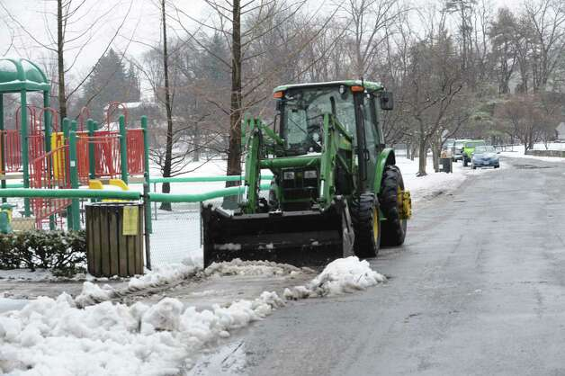 A tracker cleans snow off the road at Binney Park, in Old Greenwich, Wednesday, Jan. 16, 2013. Photo: Helen Neafsey / Greenwich Time