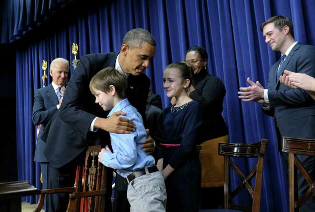 President Barack Obama, accompanied by Vice President Joe Biden, left, hugs eight-year-old letter writer Grant Fritz during a news conference on proposals to reduce gun violence, Wednesday, Jan. 16, 2013, in the South Court Auditorium at the White House in Washington. Obama and Biden were joined by law enforcement officials, lawmakers and children who wrote the president about gun violence following the shooting at an elementary school in Newtown, Conn., last month. (AP Photo/Susan Walsh) Photo: Susan Walsh, Associated Press / AP