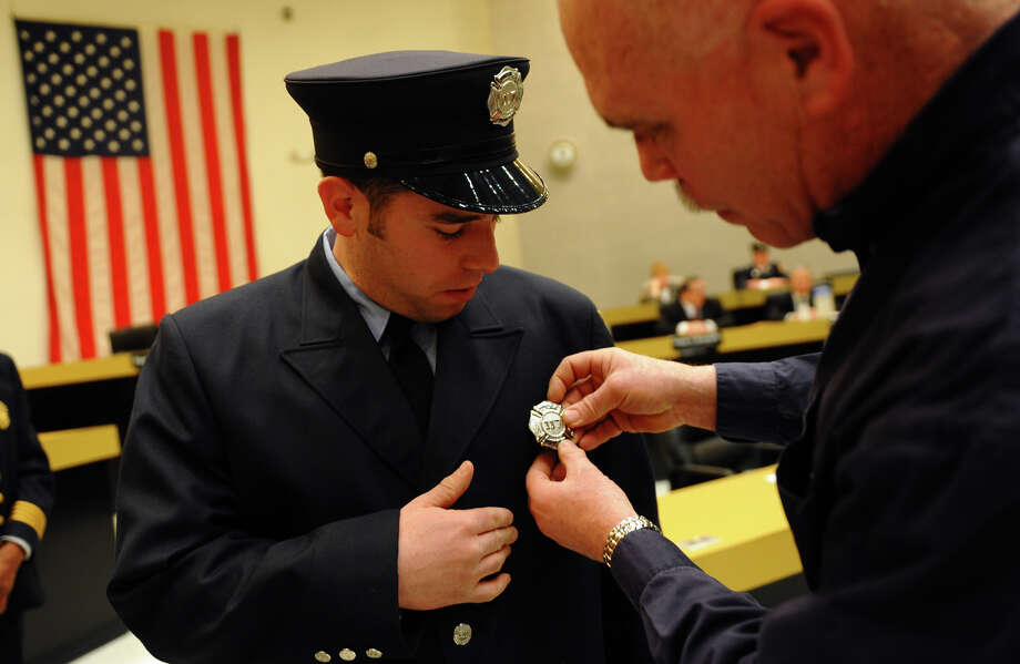 Proud dad Bruce Benedict pins on Bridgeport firefighter Kenneth Benedict's badge, during the swearing in ceremony conducted by the Board of Fire Commissioners in the Bridgeport City Council Chambers in Bridgeport, Conn. on Wednesday January 16, 2013. The 21 firefighters graduated from the Connecticut Fire Academy last month and will continue their EMS training in Bridgeport. Photo: Christian Abraham / Connecticut Post