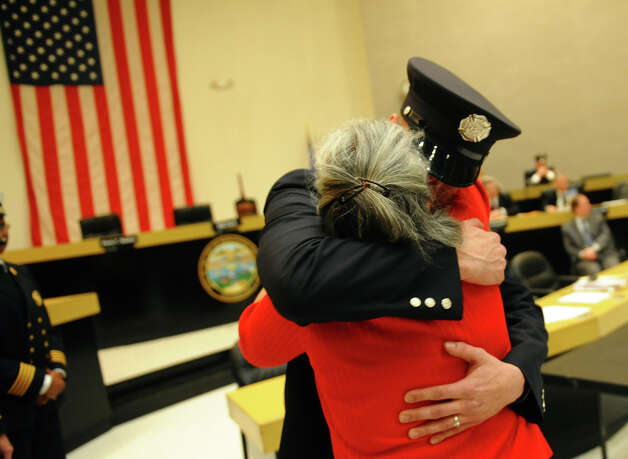 Margherita Currao hugs her son Bridgeport firefighter Derek Currao after he received his badge, during the swearing in ceremony conducted by the Board of Fire Commissioners in the Bridgeport City Council Chambers in Bridgeport, Conn. on Wednesday January 16, 2013. The 21 firefighters graduated from the Connecticut Fire Academy last month and will continue their EMS training in Bridgeport. Photo: Christian Abraham / Connecticut Post