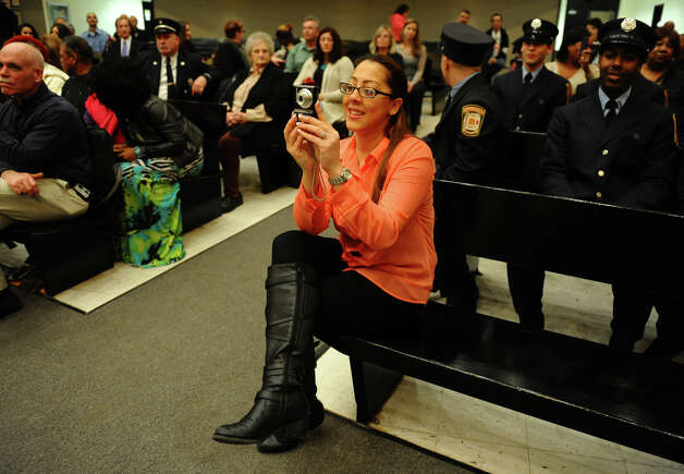 Tamara Loyola snaps pictures as her husband, Bridgeport firefighter Edgard Loyola receives his badge, during the swearing in ceremony conducted by the Board of Fire Commissioners in the Bridgeport City Council Chambers in Bridgeport, Conn. on Wednesday January 16, 2013. The 21 firefighters graduated from the Connecticut Fire Academy last month and will continue their EMS training in Bridgeport. Photo: Christian Abraham / Connecticut Post
