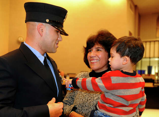 Bridgeport firefighter Edgard Loyola, left, stands with his mom Elizabeth and son Kayden, 2, after Elizabeth pinned his badge on, during the swearing in ceremony conducted by the Board of Fire Commissioners in the Bridgeport City Council Chambers in Bridgeport, Conn. on Wednesday January 16, 2013. The 21 firefighters graduated from the Connecticut Fire Academy last month and will continue their EMS training in Bridgeport. Photo: Christian Abraham / Connecticut Post