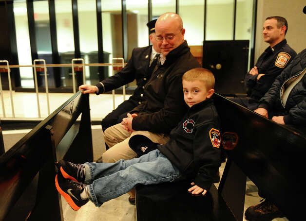 Bridgeport Fire Department Lt. David Dobbs sits with his son Jimmy, during the swearing in ceremony for 21 new firefighters conducted by the Board of Fire Commissioners in the Bridgeport City Council Chambers in Bridgeport, Conn. on Wednesday January 16, 2013. The firefighters graduated from the Connecticut Fire Academy last month and will continue their EMS training in Bridgeport. Photo: Christian Abraham / Connecticut Post