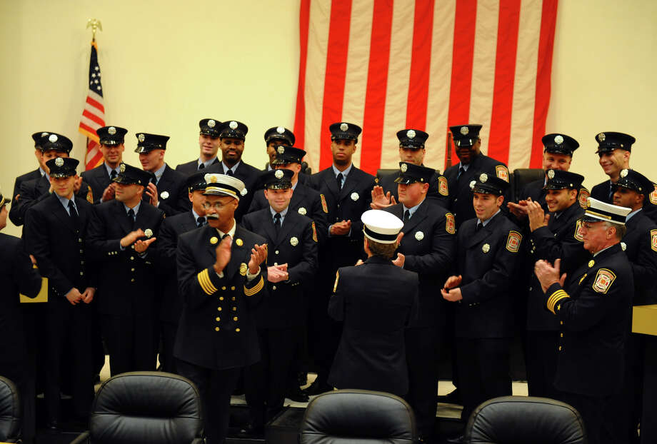 The Board of Fire Commissioners swore in 21 new firefighters in front of family and friends in the Bridgeport City Council Chambers in Bridgeport, Conn. on Wednesday January 16, 2013. The group graduated from the Connecticut Fire Academy last month and will continue their EMS training in Bridgeport. Photo: Christian Abraham / Connecticut Post