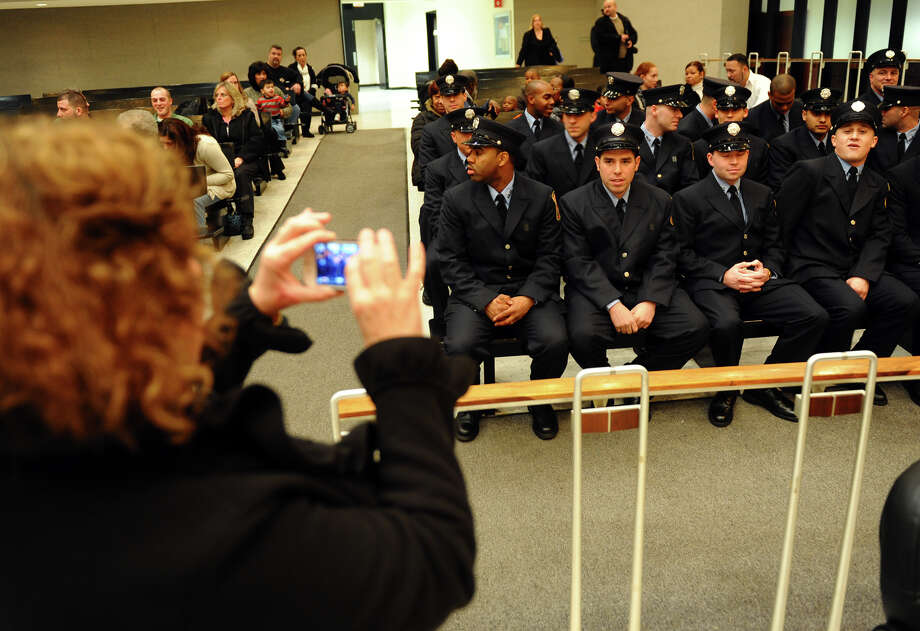 Pam Benedict snaps pictures of her son Kenneth, second from left in front row, who will shortly be sworn in as a new firefighter with 20 others, during a ceremony conducted by the Board of Fire Commissioners in the Bridgeport City Council Chambers in Bridgeport, Conn. on Wednesday January 16, 2013. The firefighters graduated from the Connecticut Fire Academy last month and will continue their EMS training in Bridgeport. Photo: Christian Abraham / Connecticut Post