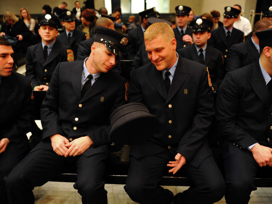 Soon-to-be new firefighter Derek Currao, left, checks out Louis DeBiase's hat, before the start of a swearing in ceremony conducted by the Board of Fire Commissioners in the Bridgeport City Council Chambers in Bridgeport, Conn. on Wednesday January 16, 2013. The 21 firefighters graduated from the Connecticut Fire Academy last month and will continue their EMS training in Bridgeport. Photo: Christian Abraham / Connecticut Post