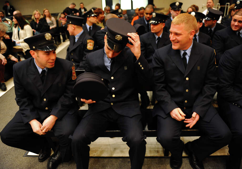 Soon to be new firefighter Derek Currao, center, tries on Louis DeBiase's hat, right, before the start of a swearing in ceremony conducted by the Board of Fire Commissioners in the Bridgeport City Council Chambers in Bridgeport, Conn. on Wednesday January 16, 2013. The 21 firefighters graduated from the Connecticut Fire Academy last month and will continue their EMS training in Bridgeport. Photo: Christian Abraham / Connecticut Post