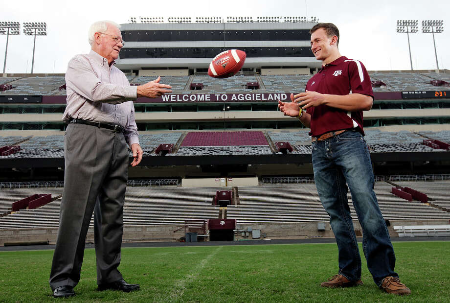 Former Texas A&M running back and 1957 Heisman Trophy winner John David Crow tosses the ball to current Texas A&M freshman quarterback and Heisman finalist Johnny Manziel on Dec. 4, 2012, at Kyle Field in College Station. Photo: Edward A. Ornelas, San Antonio Express-News / © 2012 San Antonio Express-News