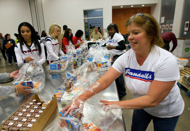 Teresa Bell, right, bags food during the kick off of Souper Bowl of Caring 2013 at the Houston Food Bank, Wednesday, Jan. 16, 2013, in Houston. The three-week effort will consist of food drives throughout the region led by community groups, schools and congregations and aims to feed the hungry. The campaing hopes to reach a collection of cash contributions and food donations equal to 3.5 million meals. Photo: Cody Duty, Houston Chronicle / © 2012 Houston Chronicle