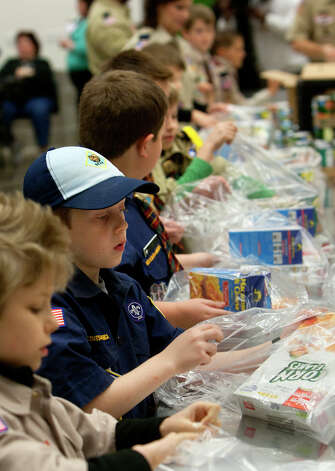 Volunteers pack food during the kick off of Souper Bowl of Caring 2013 at the Houston Food Bank. Photo: Cody Duty, Houston Chronicle / © 2012 Houston Chronicle
