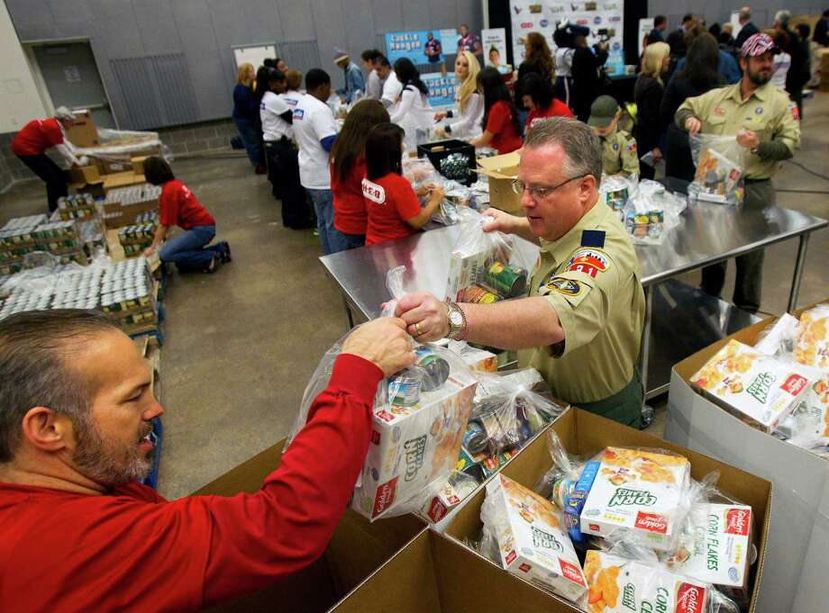 Ralph Telford, right, hands a bag of food to Kevin Glynn, left, during the kick off of Souper Bowl of Caring 2013 at the Houston Food Bank. Photo: Cody Duty, Houston Chronicle / © 2012 Houston Chronicle