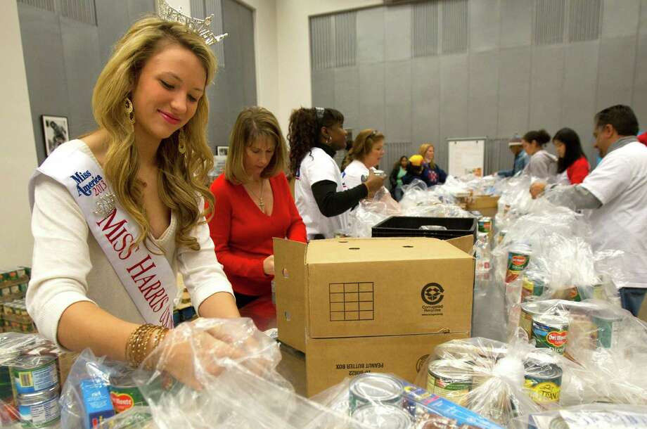 Miss Harris County Niki Noblett, left, bags food during the kick off of Souper Bowl of Caring. Photo: Cody Duty, Houston Chronicle / © 2012 Houston Chronicle