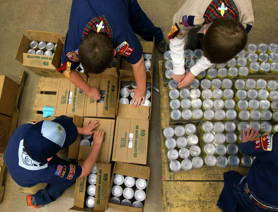 From left to right, Thomas Keener, 8,  Matthew Kut, 9, Jonathan Cain, 9, and Ben Cain, 7, open up packaged cans during the kick off of Souper Bowl of Caring 2013 at the Houston Food Bank. Photo: Cody Duty, Houston Chronicle / © 2012 Houston Chronicle