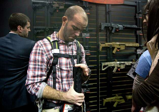 Will Michaels of Homer, La., examines a Bushmaster M4 A3 Carbine 300 AAC Blackout rifle at the Bushmaster exhibit during the Shooting Hunting Outdoor Tradeshow, Tuesday, Jan. 15, 2013, in Las Vegas. Michaels, who owns a sporting goods store, said while his gun sales focus primarily on bolt action hunting rifles, he and his clients have taken an interest in assault rifles over the last five years because of an expanding wild hog problem in his region. The National Shooting Sports Foundation was focusing its 35th annual SHOT Show on products and services new to what it calls a $4.1 billion industry, with a nod to a raging national debate over assault weapons. Photo: Julie Jacobson, (AP Photo/Julie Jacobson) / Associated Press