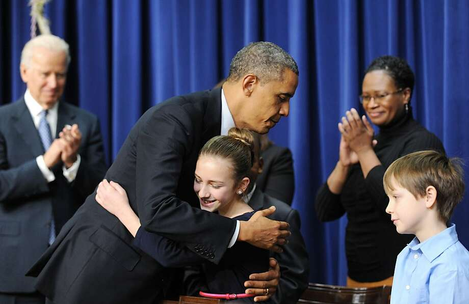 President Obama hugs Julia Stokes, one of several children who wrote him requesting he take action on guns and who joined him as he outlined his proposals at an event in Washington. Photo: Olivier Douliery, McClatchy-Tribune News Service