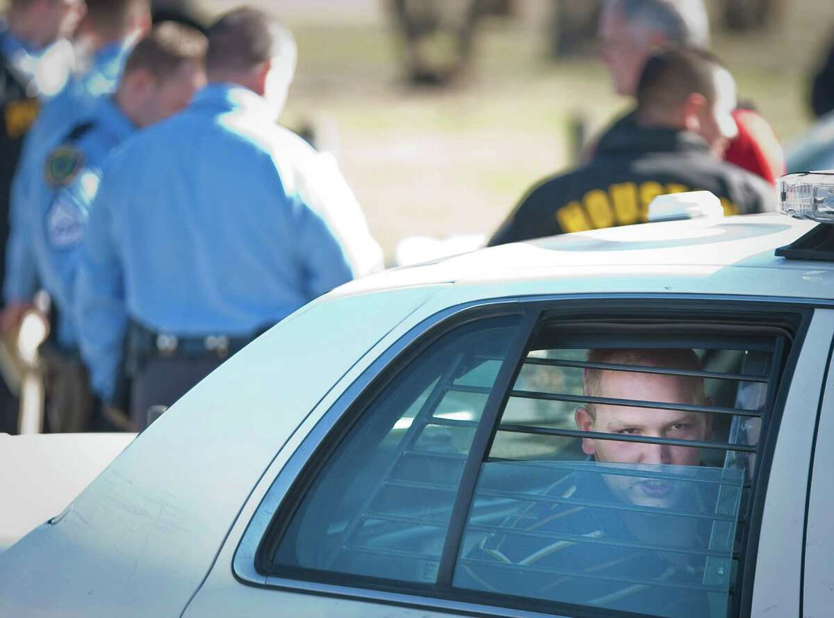 A bank robbery suspect sits in the back seat of a Houston Police Department car after leading police on a chase through out the downtown and southeast area, Wednesday, Jan. 16, in Houston.