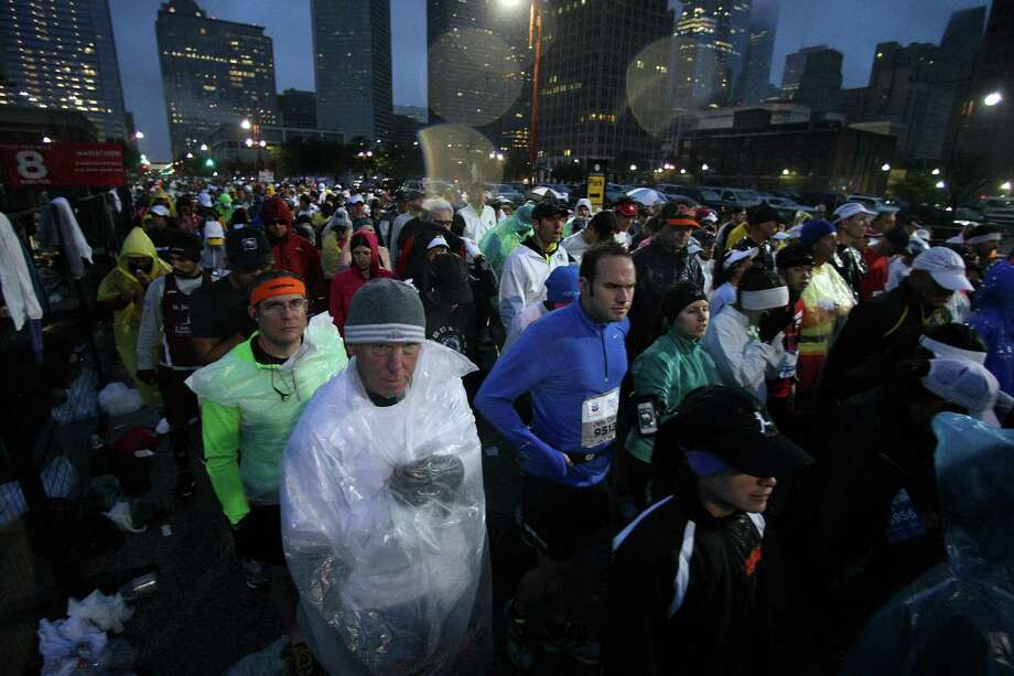 Ponchos and garbage bags were popular outerwear Sunday as rain bedeviled runners before the start and in the early hours of the Chevron Houston Marathon and Aramco Houston Half Marathon. Photo: James Nielsen, Staff / © Houston Chronicle 2013