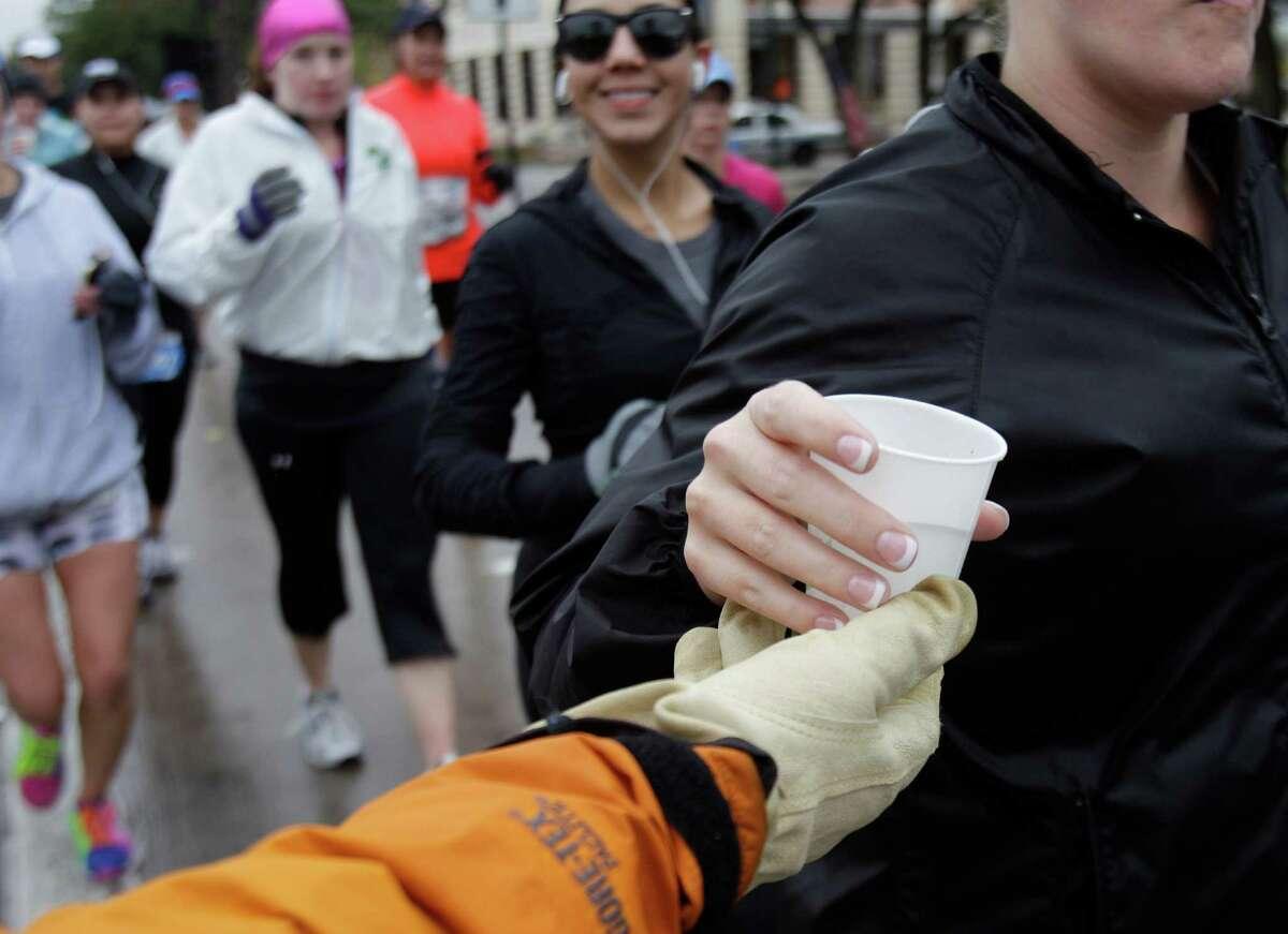 Volunteer Ronny Cuenod of Houston hands out water to runners along University near mile 13 of the Chevron Houston Marathon Sunday, Jan. 13, 2012 in West University. ( Melissa Phillip / Houston Chronicle )