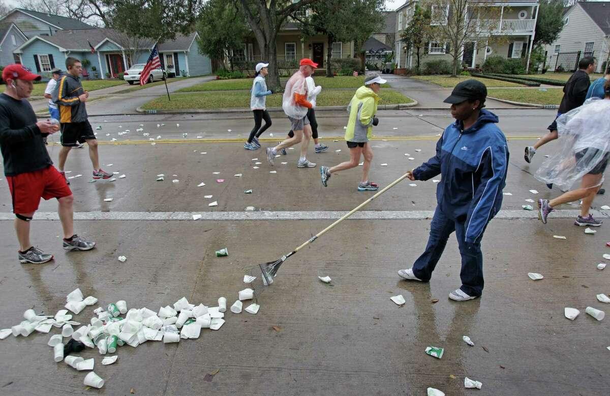 Volunteer Ashton McKinley rakes cups and other trash dropped by runners along University near mile 13 of the Chevron Houston Marathon Sunday, Jan. 13, 2012 in West University. ( Melissa Phillip / Houston Chronicle )