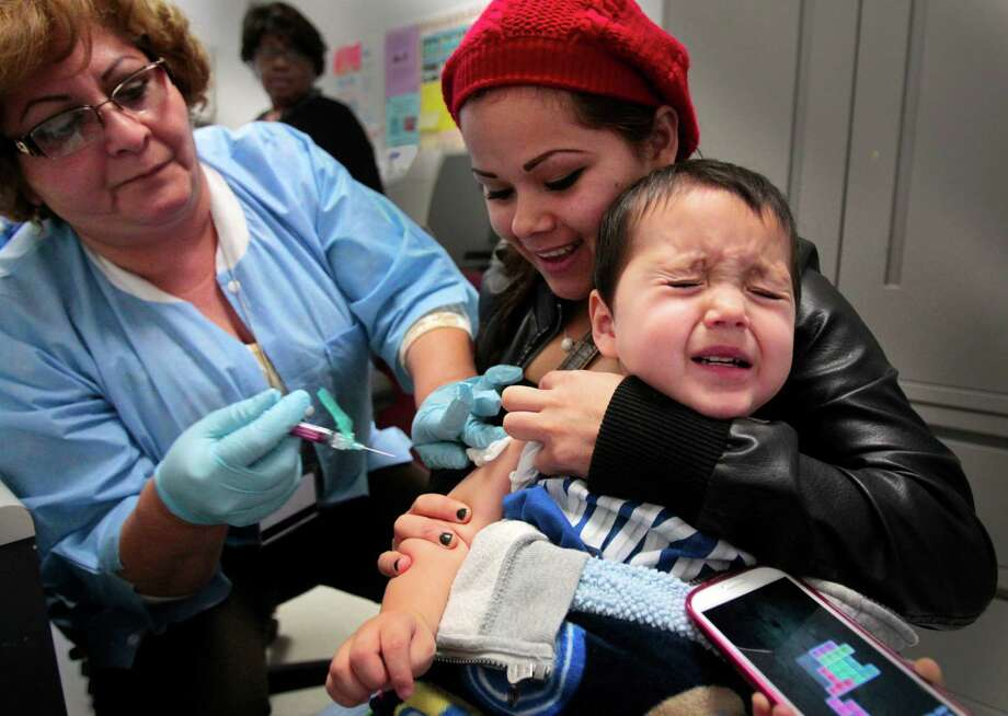 Medical Assistant Diana Cantu gives a influenza immunization to two year-old Leonardo Sanchez as his mother Zuleina Moreno braces him for the shot at Casa Health Center at 1809 North Main Street. In the month of January Casa Health Center averaged 30 flu vaccines a day.  Wednesday, Jan. 16, 2013, in Houston ( Billy Smith II / Houston Chronicle ) Photo: Billy Smith II, Staff / © 2013 Houston Chronicle