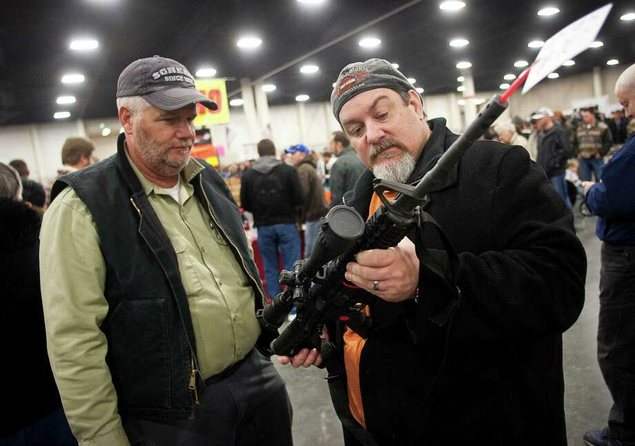 FILE - In a Saturday, Jan. 5, 2013 file photo, gun owners discuss a potential sale of an AR-15, during the 2013 Rocky Mountain Gun Show at the South Towne Expo Center in Sandy, Utah. Nearly six in 10 Americans want stricter gun laws in the aftermath of last month's deadly school shooting in Connecticut, with majorities favoring a nationwide ban on military-style, rapid-fire weapons and limits on gun violence depicted in video games and movies and on TV, according to a new Associated Press-GfK poll. A lopsided 84 percent of adults would like to see the establishment of a federal standard for background checks for people buying guns at gun shows, the poll showed. President Barack Obama was set Wednesday, Jan. 16, 2013 to unveil a wide-ranging package of steps for reducing gun violence expected to include a proposed ban on assault weapons, limits on the capacity of ammunition magazines and universal background checks for gun sales.(AP Photo/The Deseret News, Ben Brewer, File) NO SALES; MAGS OUT; SALT LAKE TRIBINE OUT;  PROVO DAILY HERALD OUT Photo: Ben Brewer
