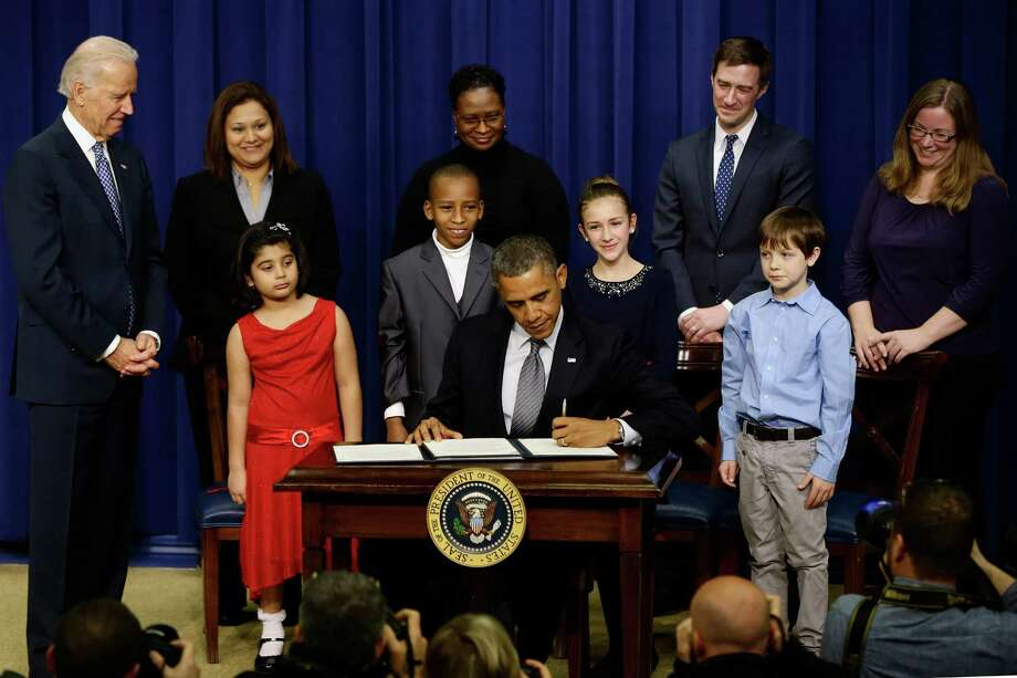 President Barack Obama, accompanied by Vice President  Joe Biden, and children who wrote the president about gun violence following last month's shooting at an elementary school in Newtown, Conn., signs executive orders to reduce gun violence, Wednesday, Jan. 16, 2013, in the South Court Auditorium at the White House in Washington. From left are: Biden Hinna Zeejah, 8, and Nadia Zeejah, HinnaâÄôs mother, Taejah Goode, 10, and Kimberly Graves, TaejahâÄôs mother, Julia Stokes, 11, and Dr. Theophil Stokes, JuliaâÄôs father, and Grant Fritz, 8. Photo: Charles Dharapak, AP Photo/Charles Dharapak / Associated Press