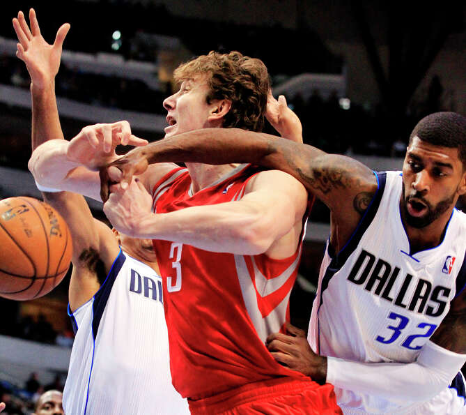 Rockets center Omer Asik is pressured under the basket by Mavericks center Chris Kaman guard O.J. Ma