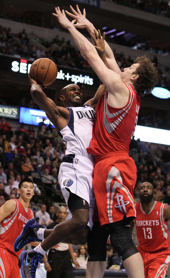 Mavericks point guard Mike James drives against Rockets center Omer Asik. Photo: Brad Loper, Staff Photographer / 20004632A
