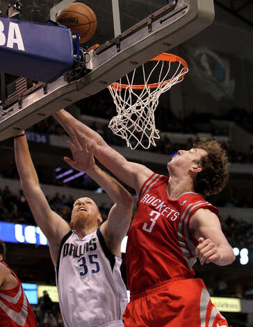 Mavericks center Chris Kaman lays in a shot past Rockets center Omer Asik. Photo: Brad Loper, Staff Photographer / 20004632A
