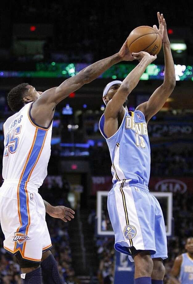 Thunder guard DeAndre Liggins knocks away a shot by the Nuggets' Corey Brewer in Oklahoma City's wire-to-wire win. Photo: Alonzo Adams, Associated Press