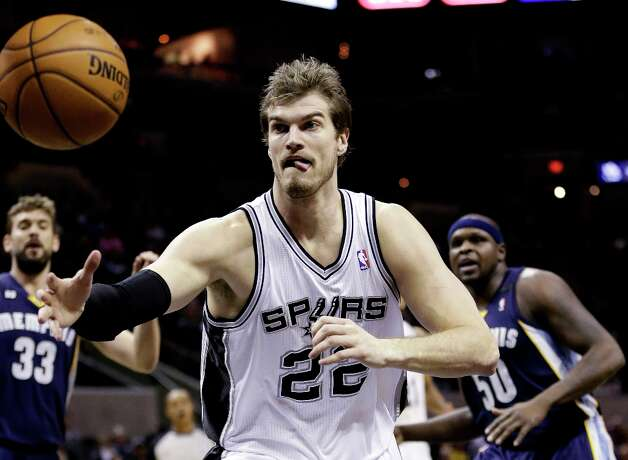 San Antonio Spurs' Tiago Splitter (22), of Brazil, chases a loose all as Memphis Grizzlies' Marc Gasol (33) and Zach Randolph (50) watch during the first quarter of an NBA basketball game, Wednesday, Jan. 16, 2013, in San Antonio. Photo: Eric Gay, Associated Press / AP