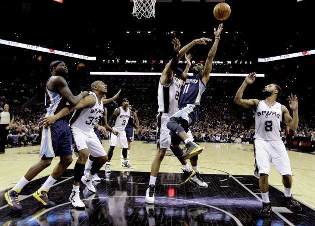 Memphis Grizzlies' Mike Conley (11) is blocked as he tries to score by San Antonio Spurs' Tim Duncan, center, during the second quarter of an NBA basketball game, Wednesday, Jan. 16, 2013, in San Antonio. The Spurs won 103-82. Photo: Eric Gay, Associated Press / AP