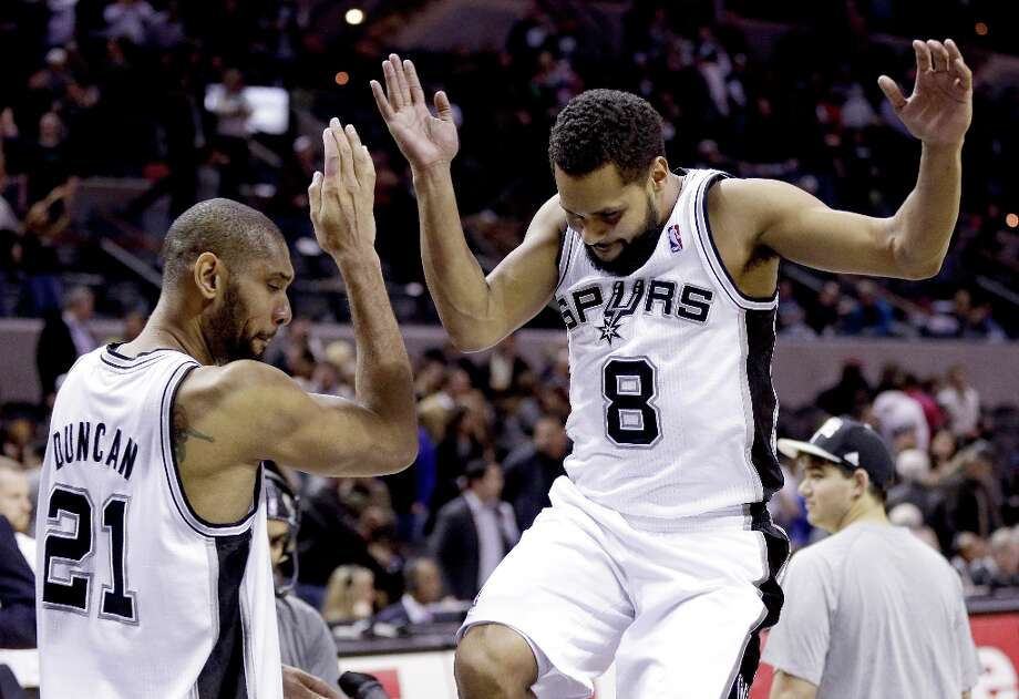 San Antonio Spurs' Tim Duncan (21) celebrates with Patty Mills (8) following their NBA basketball game against the Memphis Grizzlies, Wednesday, Jan. 16, 2013, in San Antonio. The Spurs won 103-82. Photo: Eric Gay, Associated Press / AP