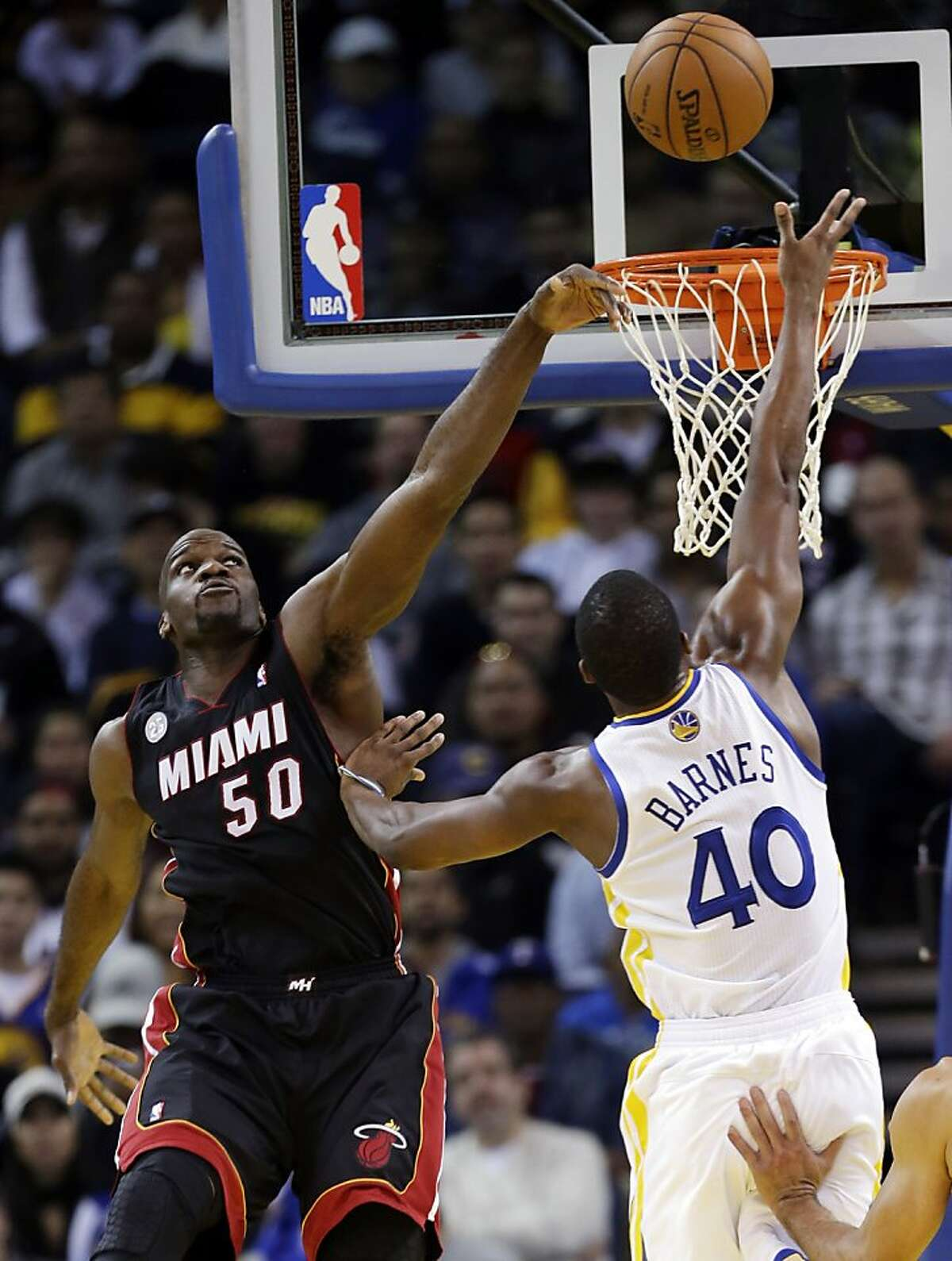 Miami Heat's Joel Anthony (50) blocks a layup attempt from Golden State Warriors' Harrison Barnes (40) during the first half of an NBA basketball game in Oakland, Calif., Wednesday, Jan. 16, 2013. (AP Photo/Marcio Jose Sanchez)