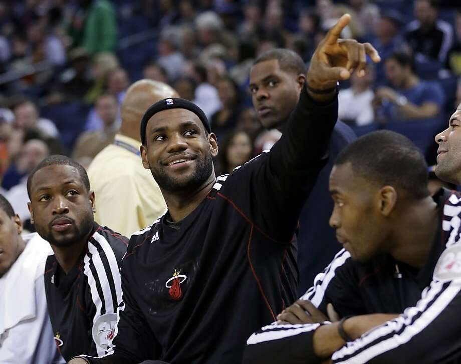 Miami Heat's LeBron James, center, acknowledges fans in the stands with teammate Dwyane Wade, left, after scoring his 20,000 career point against the Golden State Warriors during the second half of an NBA basketball game in Oakland, Calif., Wednesday, Jan. 16, 2013. James on Wednesday became the youngest player in NBA history to score 20,000 points. (AP Photo/Marcio Jose Sanchez) Photo: Marcio Jose Sanchez, Associated Press