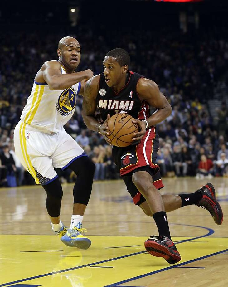 Miami Heat's Mario Chalmers, right, dribbles past Golden State Warriors' Jarrett Jack (2) during the first half of an NBA basketball game in Oakland, Calif., Wednesday, Jan. 16, 2013. (AP Photo/Marcio Jose Sanchez) Photo: Marcio Jose Sanchez, Associated Press